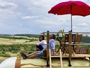 Weinerlebnis Bad Mergentheim Wildparkbus. Zwei Personen sitzen auf dem Dach eines Busses und genießen die Aussicht.