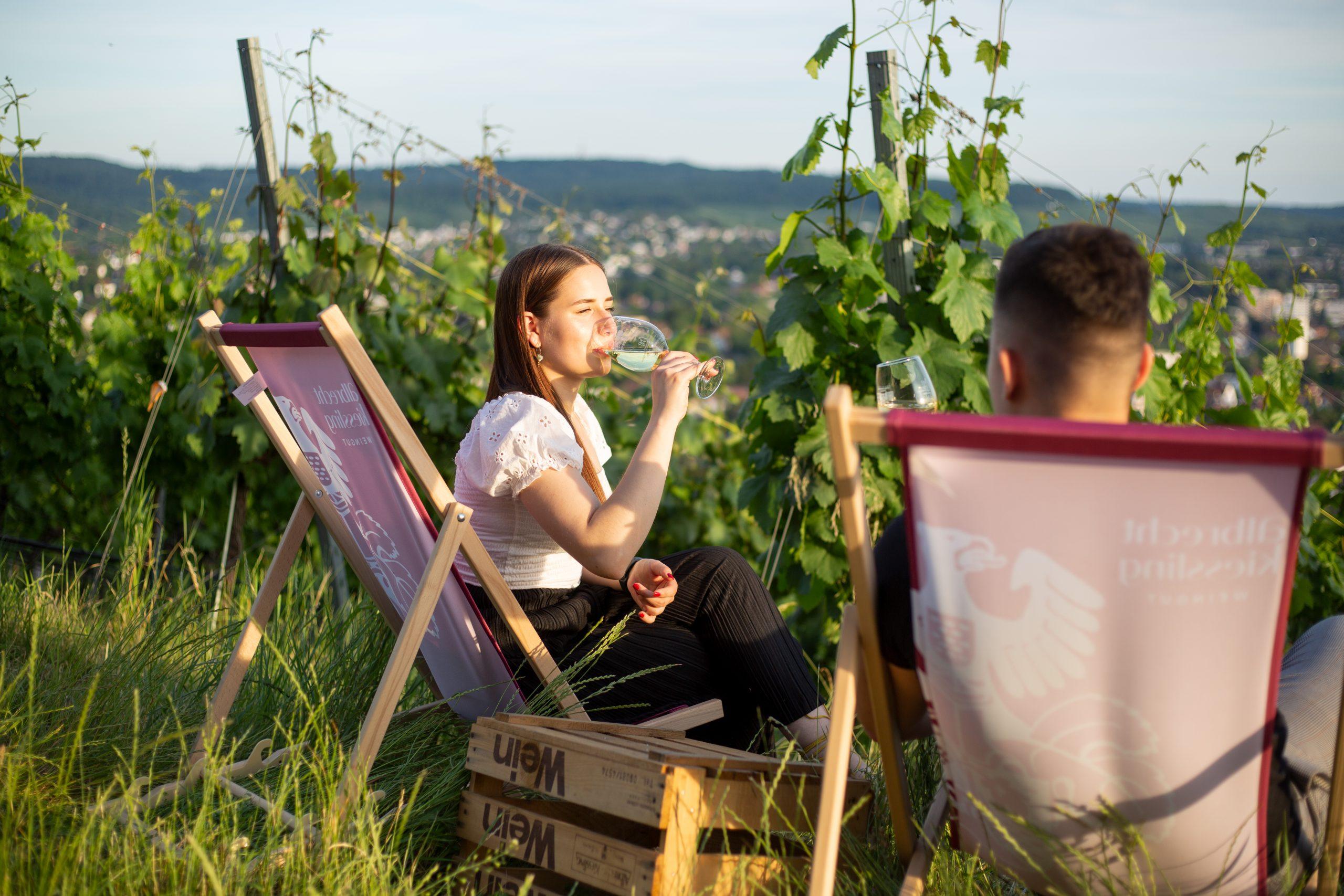 Nehmen an einem der Weinerlebnisse teil: Zwei junge Menschen sitzen im Weinberg und trinken Wein