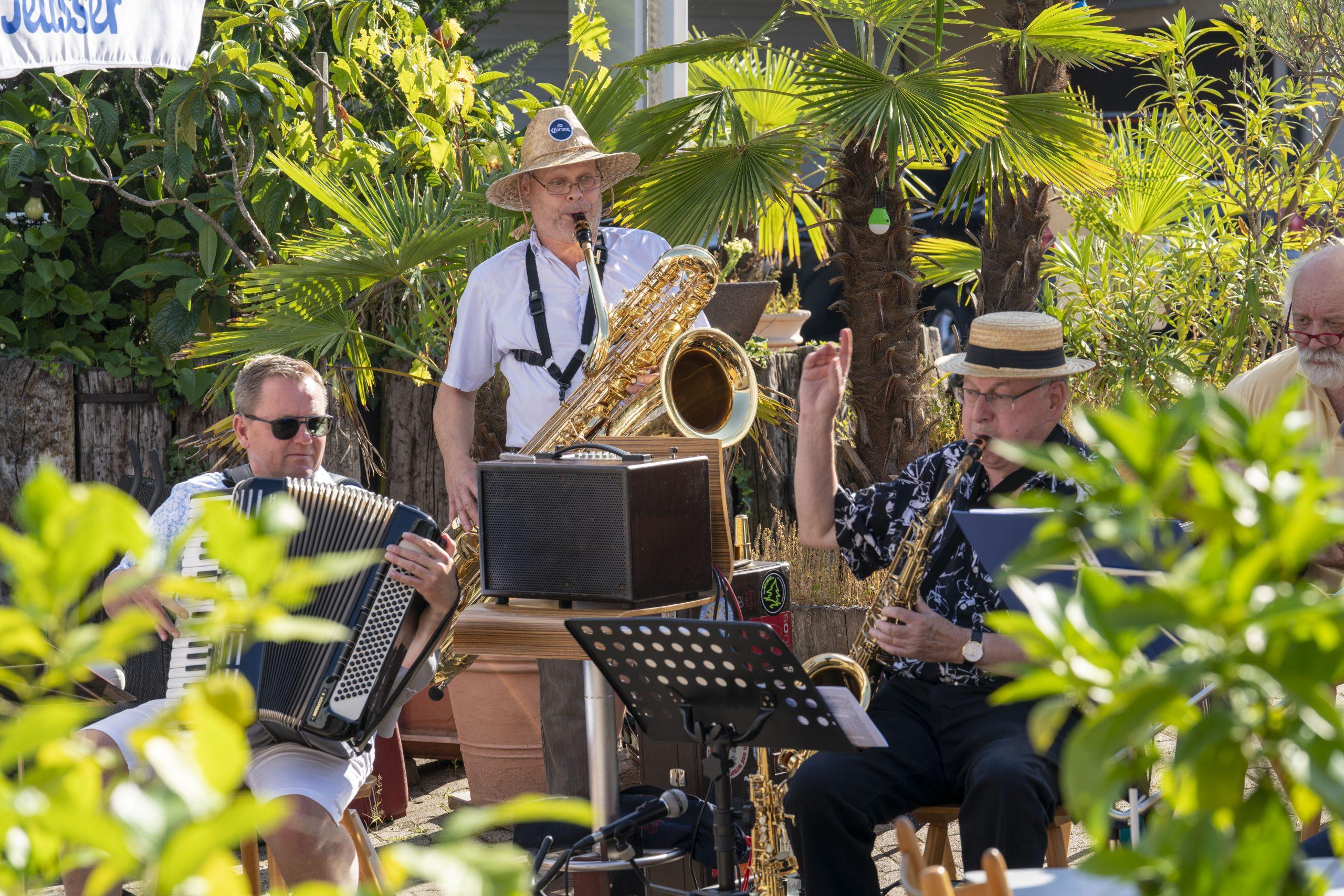 Weinerlebnis par excellence: Eine Band musiziert inmitten eines schönen Gartens