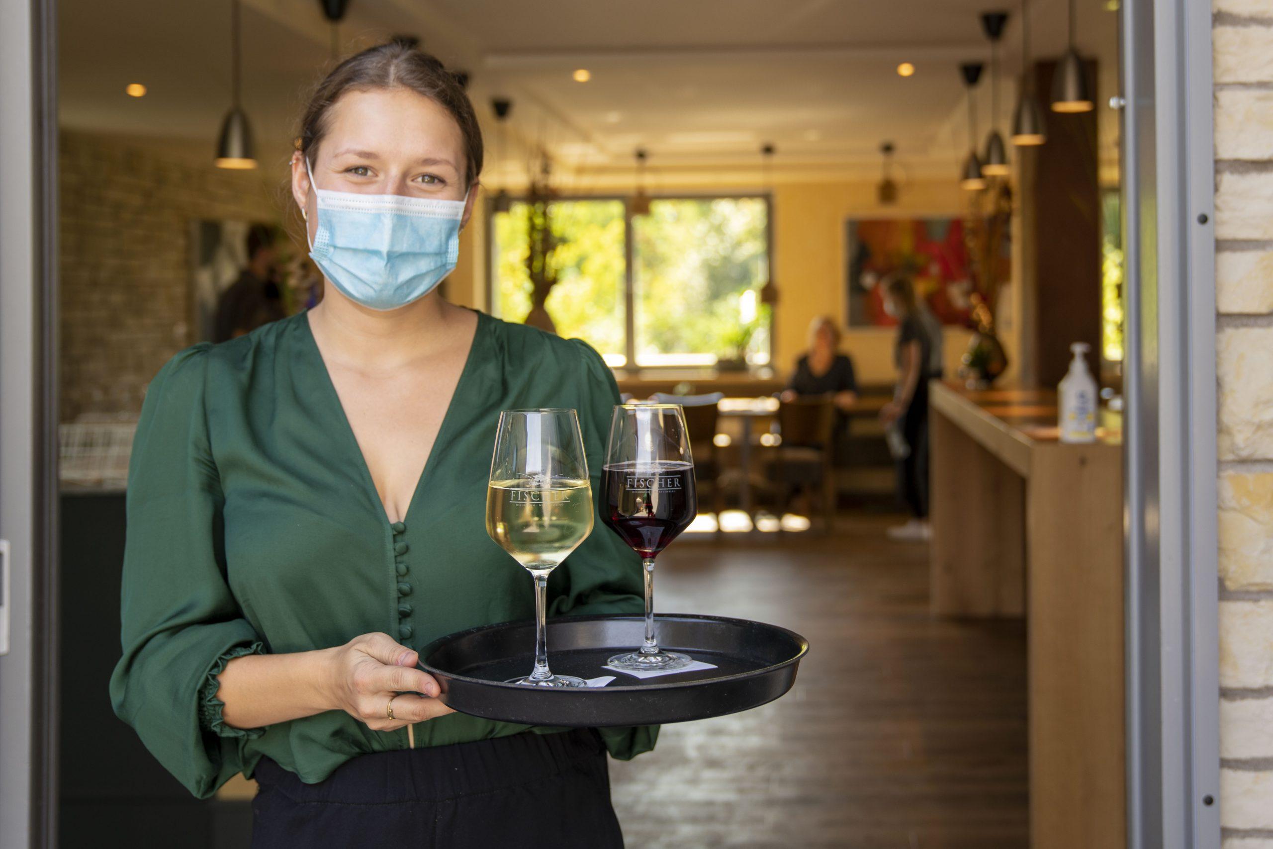 Junge Frau serviert Wein