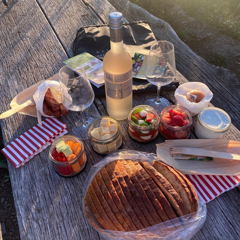 Picknick vom Feinsten: Man sieht das Weinpicknick der Weingärtner Cleebronn-Güglingen auf einem Holztisch im Freien ausgebreitet.