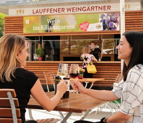 Weinausschank auf dem Kiliansplatz: Zwei Damen stoßen an vor dem Stand der Lauffeuer Weingärtner