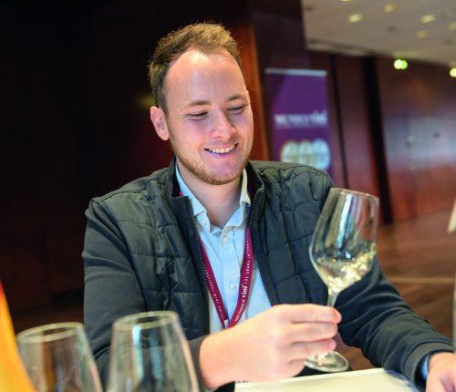 Mundus Vini: Teilnehmer schwenkt Glas und betrachtet Wein
