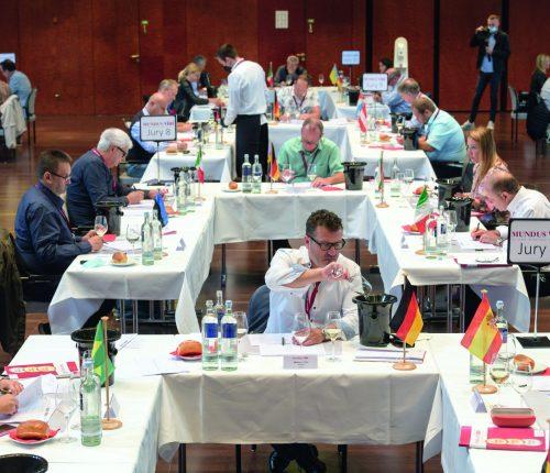 Mundus Vini: Blick auf mehrere Verkostungs-Tische mit Teilnehmern