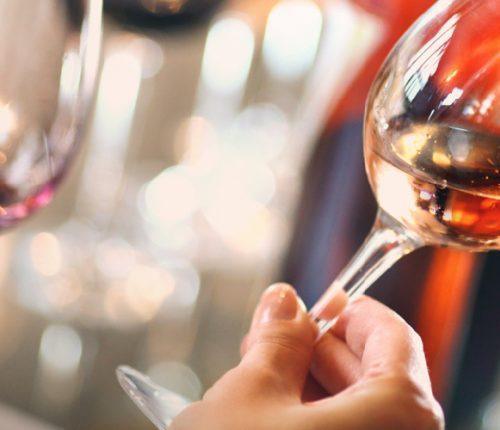 Weinverkostung, Frau hält prüfend ein Glas mit Wein in der Hand